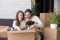 Gift par som sitter på soffan och packar upp kartonger royaltyfria bilder