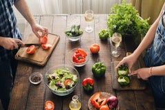 Gift par som tillsammans lagar mat matställegrönsaksallad i hem arkivbild