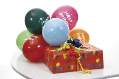 Gift parcels and balloons on table Stock Images