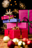 Gift Parcels Piled up amidst Baubles and Stars. Focus on a stack of four Christmas presents with golden bows. Narrow depth of field. Xmas glitter balls, twinkles Royalty Free Stock Images