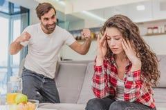 Gift parsammanträde på Gray Bed och att argumentera Stående av ilskna makeskrin på att gråta den besvikna frun under a royaltyfri foto