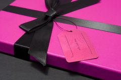 Gift in a pink box. Gift or present with pink box and a black ribbon and empty label Royalty Free Stock Photos