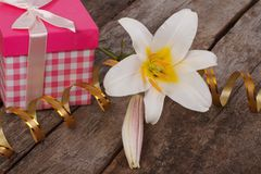 Gift pink box and a white lily flower. On the table Stock Photo