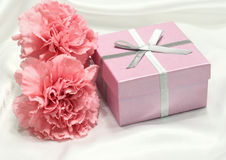 Gift with Pink Carnations on White Satin. Gift box with silver ribbon and two pink carnations Royalty Free Stock Photo