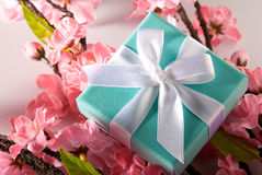 Gift with pink flower and green leaves. An aqua/blue gift knotted in a bow with a white ribbon.Pink flower and green leaves decorates Royalty Free Stock Photography