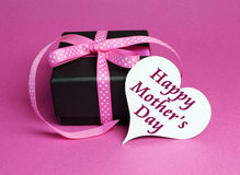 Gift with pink polka dot ribbon and white heart shape gift tag with Happy Mothers Day. Special small black box present gift with pink polka dot ribbon and white Royalty Free Stock Images