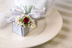 Gift on Place Setting. Elegant silver gift box adorned with silver ribbon and red velvet rose on white china plate stock photo