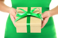 Gift / present. Woman hands showing and giving gifts. Closeup of present made of recycled carton and green ribbon on white background Royalty Free Stock Photos