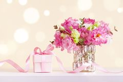Gift or present box and beautiful flowers bouquet in vase on pastel bokeh background. Greeting card for Mother day stock photos