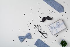 Gift or present box, bowtie, moustache, glasses and confetti for Happy Father day. Top view and flat lay