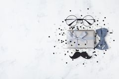 Gift or present box, bowtie, moustache, glasses and confetti for Happy Father day. Top view and flat lay. Style royalty free stock image