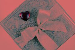 Gift or present box in colour of living coral for Valentines day stock photos