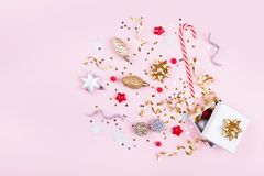 Gift or present box with confetti stars, golden ribbon and holiday decoration on pastel pink background. Christmas flat lay. stock image