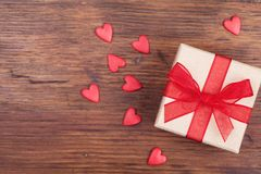 Gift or present box decorated bow ribbon and red hearts on wooden rustic table top view. Valentines or Mother day greeting card. Royalty Free Stock Photo