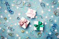 Gift or present box decorated colorful confetti, star and streamer on blue vintage table top view. Flat lay style. Christmas. Stock Images