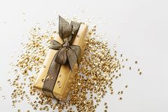 Gift or present box and golden sequins on table top view. Composition for Christmas or birthday. Stock Photo