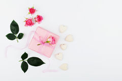Gift or present box, hearts and pink rose flower on white table top view in flat lay style for greeting card on Womans day. Royalty Free Stock Photography