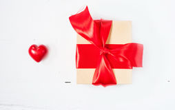 Gift or present box with red bow ribbon and ceramic heart on wooden table for Valentines day Stock Photo