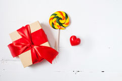 Gift or present box with red bow ribbon and ceramic heart on wooden table for Valentines day Royalty Free Stock Images
