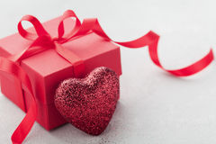 Gift or present box with red bow ribbon and glitter heart on white table for Valentines day. Stock Photo