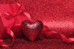 Gift or present box with red bow ribbon and heart on glitter background for Valentines day. Stock Photo