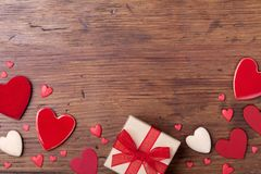 Gift or present box and red mixed hearts on rustic table top view. Valentines day greeting card. stock photography