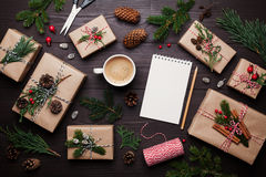 Gift or present box wrapped in kraft paper with christmas decoration, cup of coffee and empty notebook on wooden table from above. Stock Photo