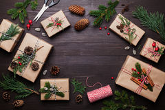 Gift or present box wrapped in kraft paper with christmas decoration on rustic wooden background from above. Flat lay style. Royalty Free Stock Images
