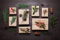 Gift or present box wrapped in kraft paper with christmas decoration on rustic wooden table from above. Flat lay style. Stock Image