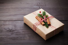 Gift or present box wrapped in kraft paper with christmas decoration on vintage wooden table. Copy space for text. Stock Photo