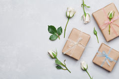 Gift or present box wrapped in kraft paper and rose flower on gray table from above. Flat lay styling. Copy space for text. Royalty Free Stock Image