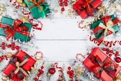 Gift or present boxes, snowy fir tree and christmas decorations on white wooden table top view. Flat lay royalty free stock photo