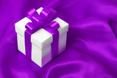 Gift on purple satin background Stock Images