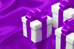 Gift on purple satin background Royalty Free Stock Photos