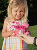 Gift Receive. Pretty little blond girl in sundress receiving a pink birthday present outdoors in summer Royalty Free Stock Images