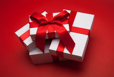 Gift with red bow. On red background Stock Images