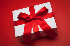 Gift with red bow. On red background Stock Image