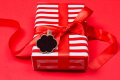 Gift with red bow. On red background. Free space for your text Stock Photos