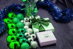 A gift with a red bow among decorative balls lies on a Christmas tree.  Stock Photography