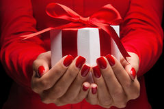 Gift with red bow in female hands Royalty Free Stock Image