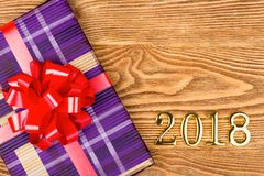 Gift with a red bow and figures 2018. On a wooden background Royalty Free Stock Image