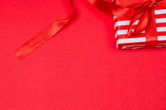 Gift with red bow. On red background. Free space for your text Royalty Free Stock Photos