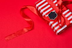 Gift with red bow. On red background. Free space for your text Royalty Free Stock Photography