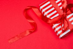 Gift with red bow. On red background. Free space for your text Royalty Free Stock Photo