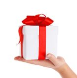 Gift with red bow in hand. Isolated on white background Stock Photos