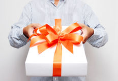 Gift with red bow in hand Royalty Free Stock Photo