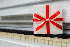 Gift with a red bow is on the keys. A gift with a red bow is on the keys, closeup Stock Image
