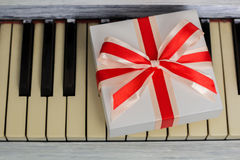 Gift with a red bow is on the keys. A gift with a red bow is on the keys, view from above Royalty Free Stock Image
