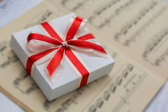 Gift with red bow lying on sheet music. Closeup Stock Image