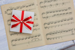 Gift with red bow lying on sheet music. View from above Royalty Free Stock Photo